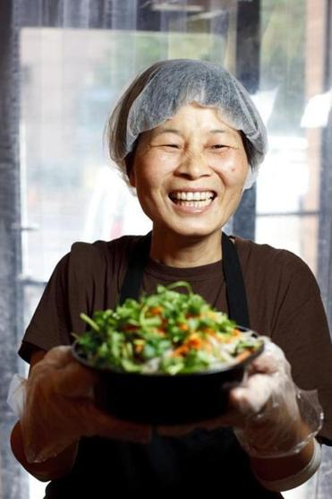 Fang, a cook at Gene's Chinese Flatbread Cafe, holds the No. 9, cumin lamb on hand-pulled noodles.